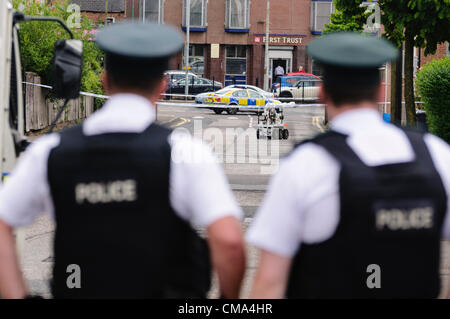 Belfast 02/07/2012 Belfast - Police officers watch an army bomb disposal robot investigate a suspicious device - Stock Photo