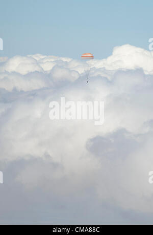 The Soyuz TMA-03M spacecraft is seen passing through clouds as it lands with Expedition 31 Commander Oleg Kononenko - Stock Photo