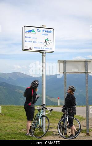 05.06.2012. Pyrenees Mountains, France.  Two cyclists looking at a sign on Col d'Aspin mountain pass (1489m) in - Stock Photo
