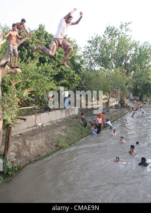 People take bath to beat the heat at a canal, on a hot day of  summer season in Lahore on Wednesday, July 04, 2012. - Stock Photo