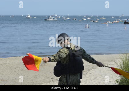 Niantic, CT - July 6, 2012: U.S. Navy Petty Officer 2nd Class Indir Kadrija, the Ramp Marshall, guides a US Navy - Stock Photo