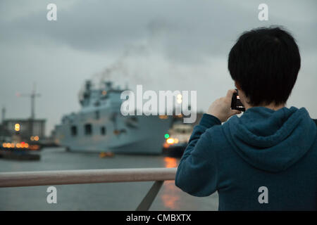 London, UK. 13th July 2012 A member of the public takes a picture of HMS Ocean, the largest in the Navy as it moored - Stock Photo