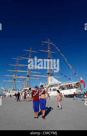 Two young women with Polish flags on their faces by the Dar Mlodziezy tall ship in harbour at Lisbon, Portugal. - Stock Photo