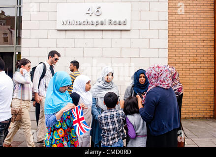 London, UK - 21 July 2012: Muslim children right after the passage of the Olympic torchbearer in Whitechapel Rd - Stock Photo