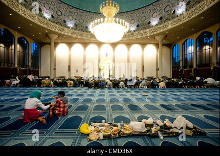 London, UK - 21 July 2012: Two children sit near a banquet while Muslim faithful pray after breaking the fast of - Stock Photo