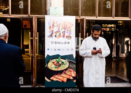 London, UK - 21 July 2012: A Muslim faithful stands by a billboard at the Ramadan Iftar 2012 celebrations hosted - Stock Photo