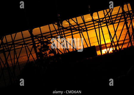 21st July 2012, Silverstone, UK.  The sun sets through the Pit Straight grandstand during the Group C race at Silverstone - Stock Photo