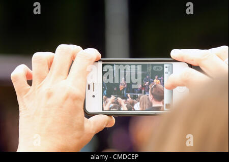 A fan takes pictures and video on a mobile phone of Rock star / musician John McCrea of the alt rock  indie rock - Stock Photo