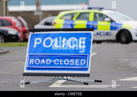 Police road closed sign with police car blocking the road - Stock Photo
