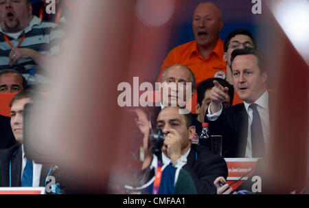 Russian President Vladimir Putin (centre) and British Prime Minister David Cameron watch the men's 100-kg judo competition - Stock Photo