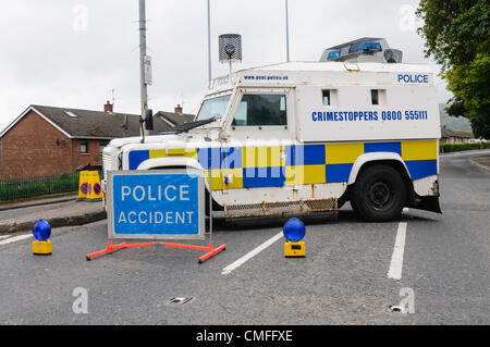PSNI police armoured Landrover blocks a road which has been closed.  Sign says 'Police Accident' - Stock Photo