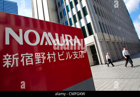 August 3, 2012 - Tokyo, Japan - Businessmen walk out the the Nomura Holdings Inc. building in the Shinjuku district - Stock Photo