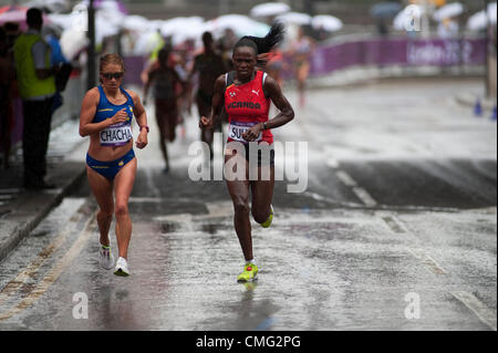 The London Olympic Games 2012 Womens Marathon runners approach the City of London from The Embankment in torrential - Stock Photo
