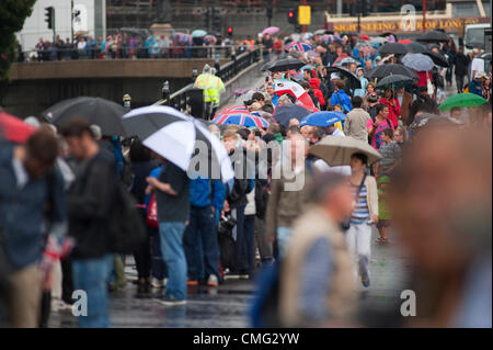 Tens of thousands of spectators line the London 2012 Womens Marathon route in central London under grey skies and - Stock Photo
