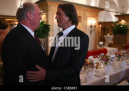 MUNICH, GERMANY - AUGUST 16:  Hans-Wilhelm Mueller Wohlfahrt (R) welcomes Uli Hoeness, president of FC Bayern Muenchen - Stock Photo