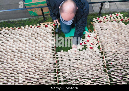 London, UK. 4th Nov, 2013. A volunteer from The Royal British Legion plants Tribute Crosses in the Field of Remembrance - Stock Photo