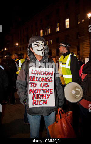 London, UK. 05/11/13. An activist holds a placard, as over a 1000 activists from various anti-Austerity groups protest - Stock Photo