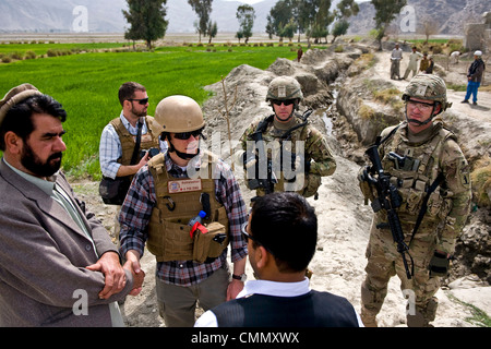 US soldiers provide protection for advisors with the Nagarhar Agribusiness Development Team and USAID during a field - Stock Photo