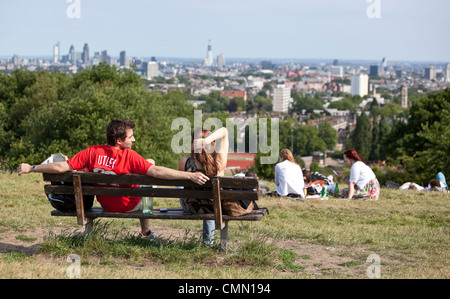 A group of people contemplating a view of the London skyline from the top of Parliament Hill, Hampstead Heath, England, - Stock Photo