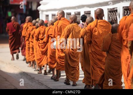 Young Buddhist monks walking around the Boddhanath stupa Kathmandu Nepal - Stock Photo
