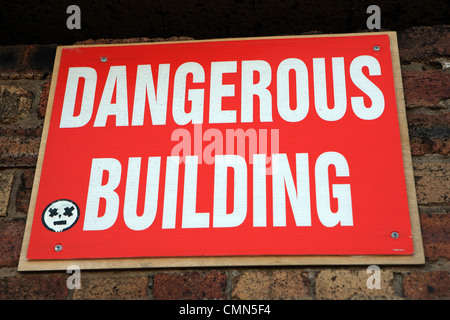 Dangerous building sign on an old building wall - Stock Photo