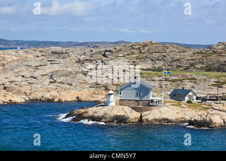 Summer house and lighthouse at Swedish weast cost - Stock Photo
