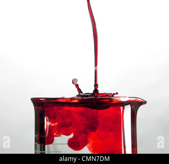 A close up of a glass medical beaker with red colored fluids pouring in - Stock Photo