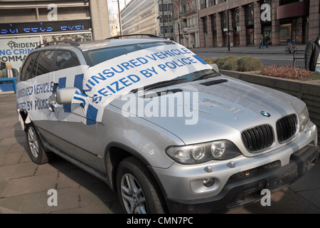 A dramatically tape-covered uninsured car seized by Police on display outside New Scotland Yard in Westminster, - Stock Photo