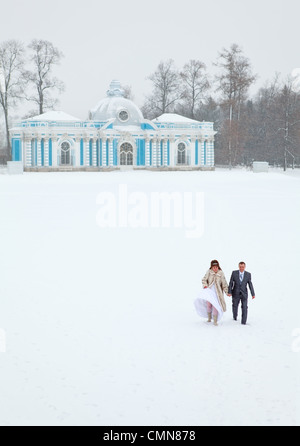 Just married walking on freezing lake area to Catherine Park near the Grotto. Pushkin city, Russia - Stock Photo