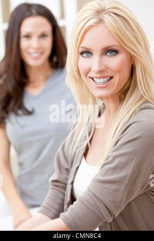 Two beautiful young women friends at home sitting on sofa or settee smiling - Stock Photo