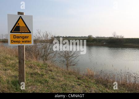 Danger Deep Water Warning Sign on a farm reservoir. - Stock Photo