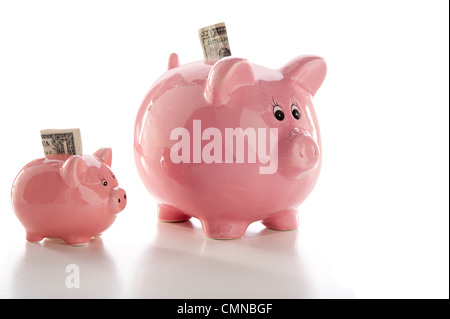 Close-up of two piggy banks, one little one and one large one, with money extending from them - Stock Photo