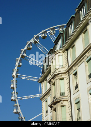 Wheel roundabout behind old white building by beautiful weather in Geneva, Switzerland - Stock Photo