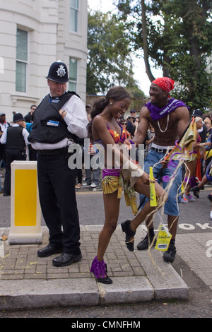 A policeman looks on at a dancer at the Notting Hill Carnival, London. - Stock Photo