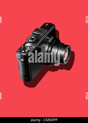 A black camera on a red background - Stock Photo