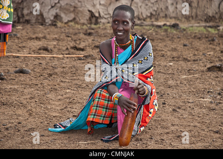Masai woman, wearing colorful traditional clothes, stirring a cow's blood in a gourd to remove the clots before - Stock Photo