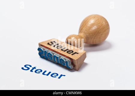 Detailansicht eines Stempels mit der Aufschrift Steuer | Detail photo of a stamp with inscription in German tax - Stock Photo