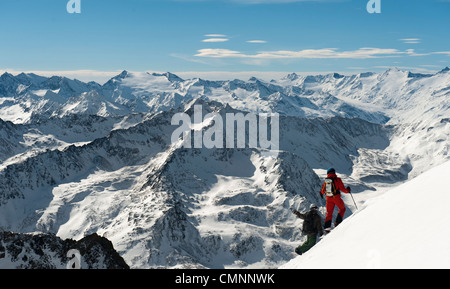 Two free skiers admiring the wintery mountain landscape at Stubai, Austria. - Stock Photo
