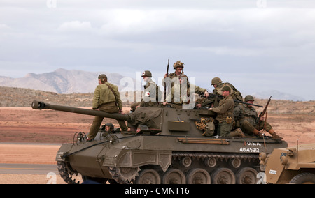 Army troops riding on top of vintage antique World War II US tank during a display in desert setting. - Stock Photo