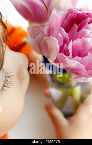 Little girl smelling the scent of  two purple flowers. - Stock Photo