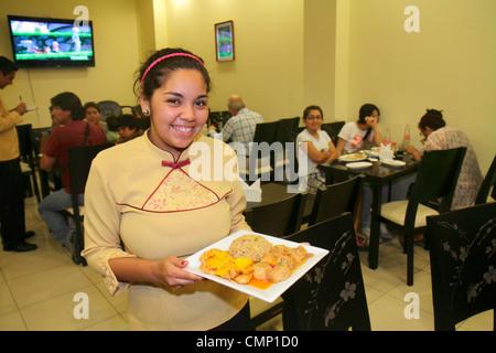 Chile Arica restaurant Chinese food ethnic dining waitress job uniform square plate serve Hispanic woman customers - Stock Photo