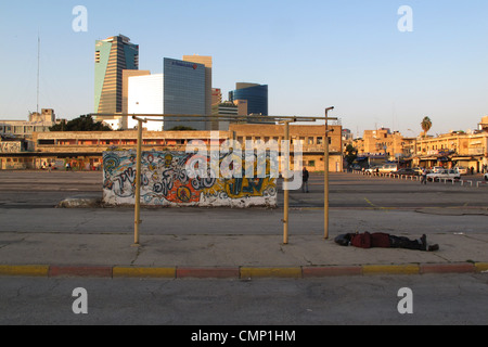 Homeless person sleeping at the old bus station in Neveh Shaanan neighborhood at the old central bus station which - Stock Photo