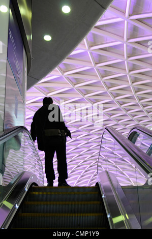 Public transport silhouette of person on indoor escalator at London train station with illuminated roof panels above - Stock Photo