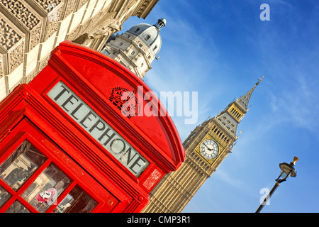A bright red telephone box at an angle in front or Parliament in Westminster - Stock Photo