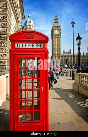 A bright red telephone box in front or Parliament in Westminster - Stock Photo