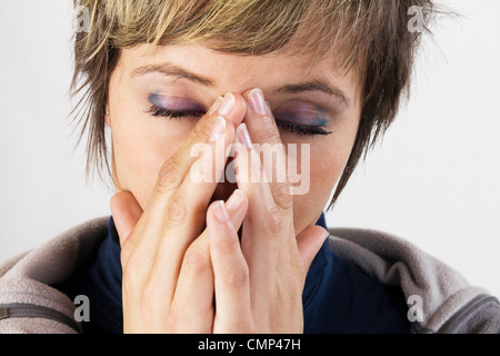 Exhausted young woman holding her hands in front of her her face - female portrait with closed eyes. Studio shot - Stock Photo