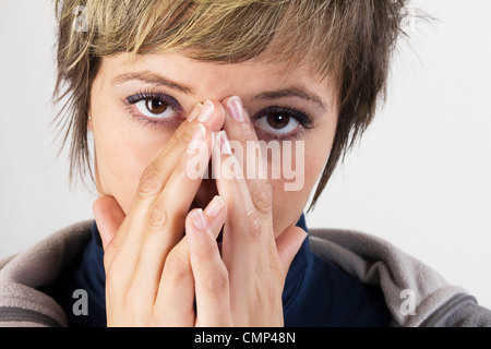 Exhausted young woman holding her hands in front of her her face, looking at the camera. Studio shot against a white - Stock Photo