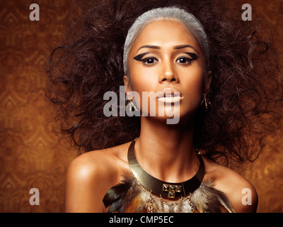 Exotic beauty portrait of a young woman with bird theamed styling and accessories - Stock Photo