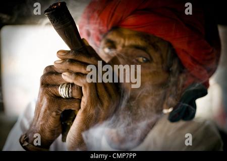 Rabari man smoking chilum(clay pipe). Photo taken at countryside near Abu Road, Rajasthan, India. Stock Photo