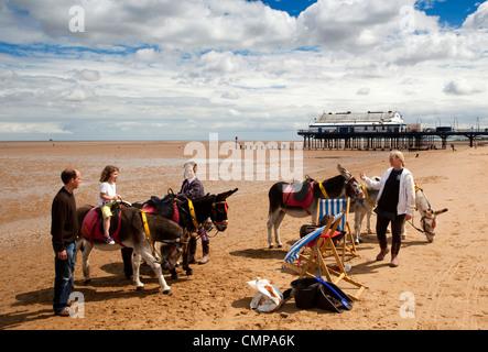 UK, England, Lincolnshire, Cleethorpes, beach, visitors enjoying donkey rides in sunshine beside the pier - Stock Photo